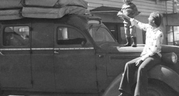 Bjørn som står på oppå Volvoen, og Far Terje Henriksen som passer på. Bilen er full lastet med madrasser.